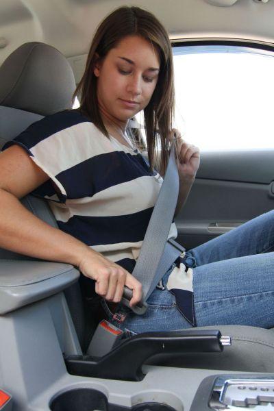 A Woman buckling her seatbelt in a car.