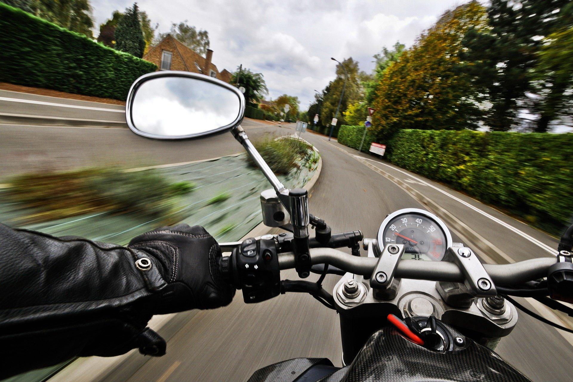 Motorcycle speeding down road.