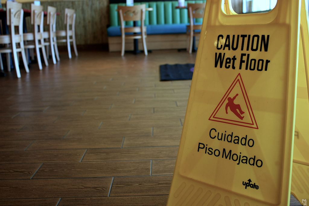 A caution wet floor sign inside a restaurant.