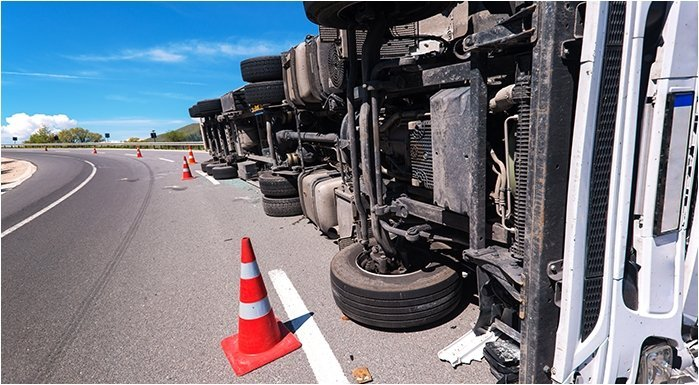 an overturned semi-truck on the side of a highway