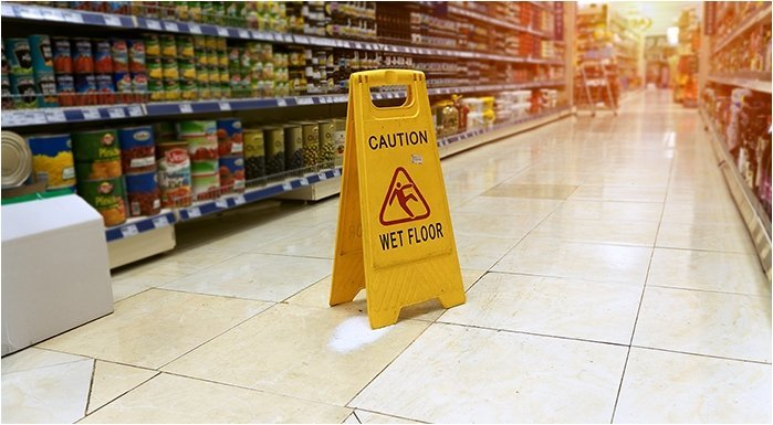 a 'caution - wet floor' sign in a grocery aisle