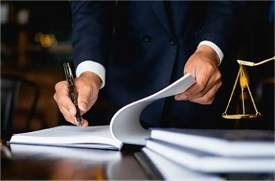Legal image of man writing on pad of paper